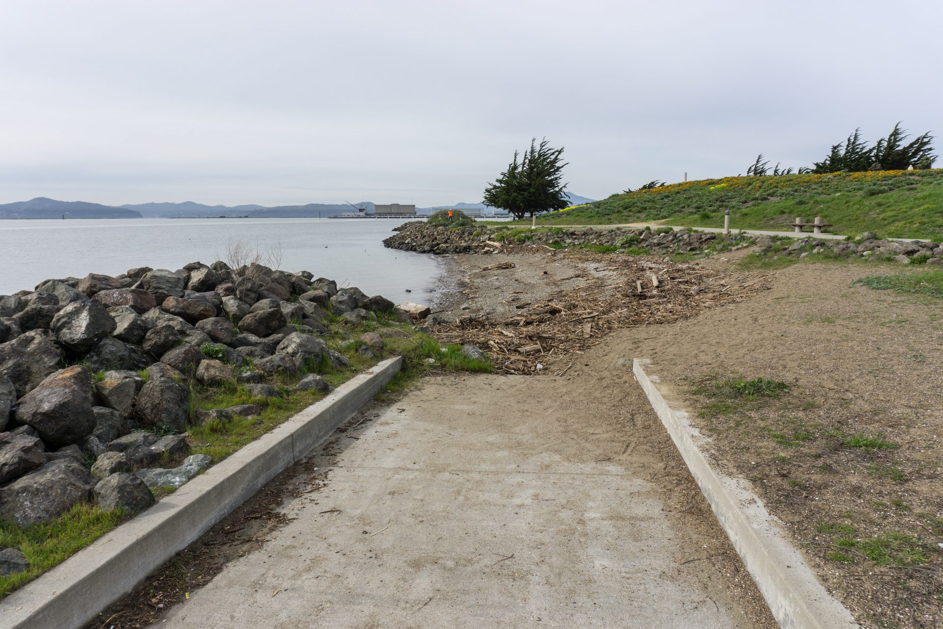 Paved path ends at abrupt drop to sandy beach
