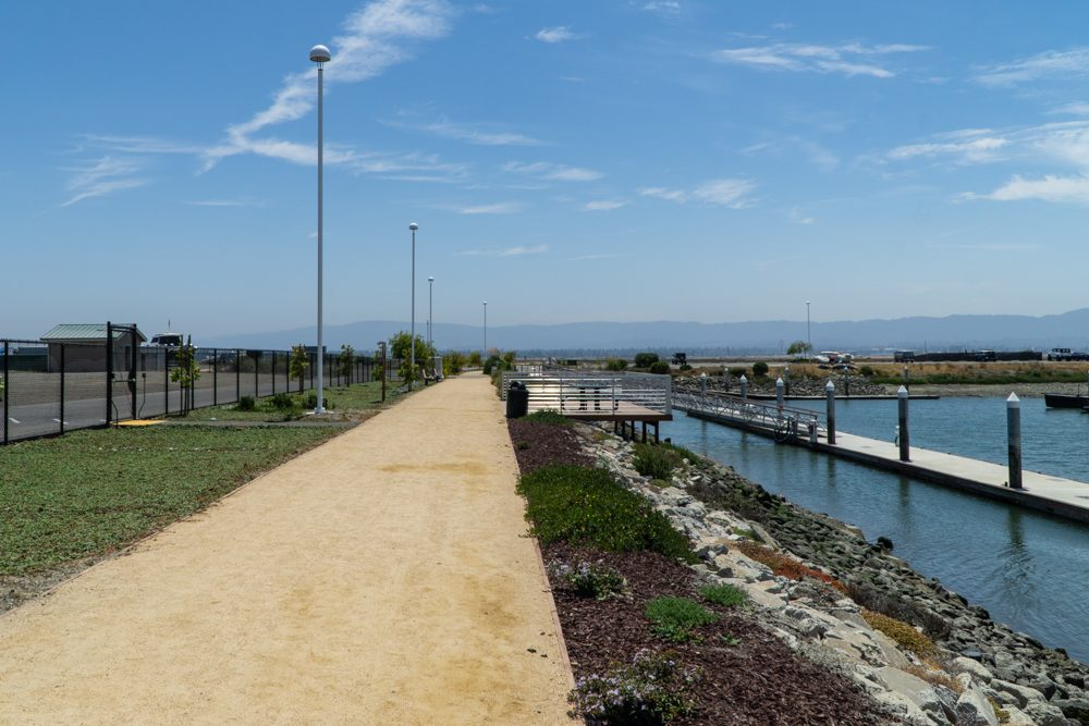 flat dirt path, grass on left and landscaping and riprap on right to bay