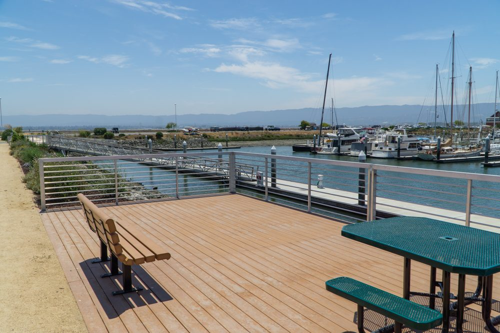 Bench and picnic table on deck overlooking marina