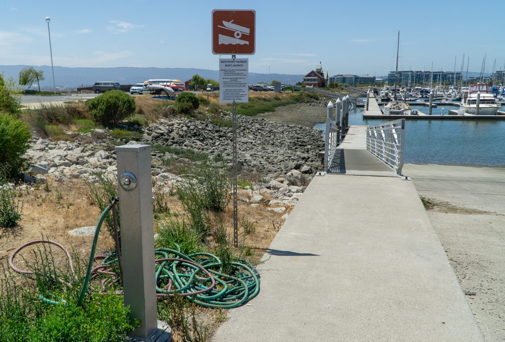Hose, boat launch sign on left, ramp to water on right