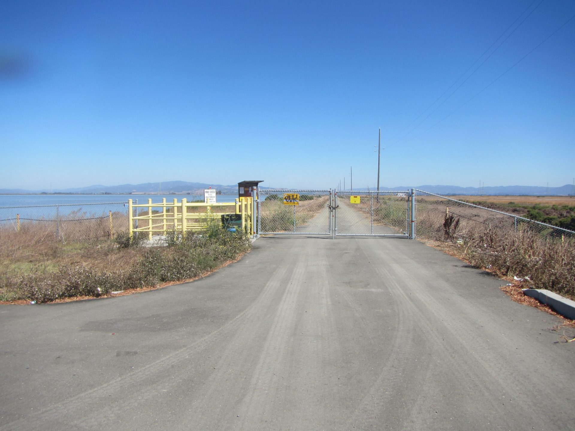gravel road and locked chainlink fence